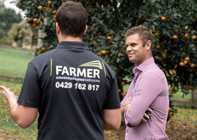 Dani Farmer speaking with customer Matt with an orchard in the background