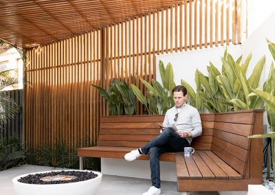 Home owner James sitting with a coffee and magazine in the new outdoor area